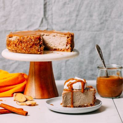 Slice of Vegan Chai Cheesecake next to a jar of caramel sauce and the remaining cheesecake