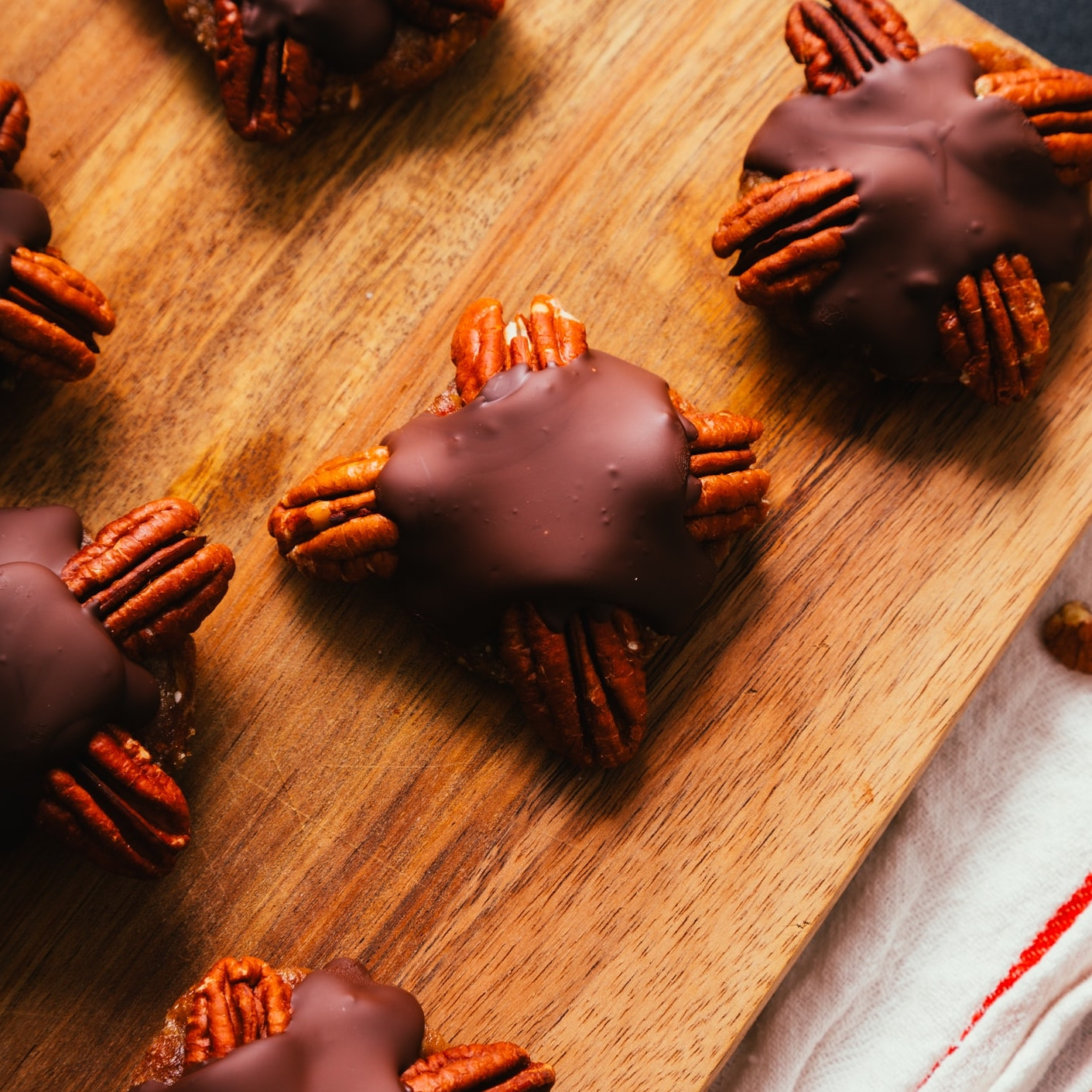 Delicious homemade Vegan Chocolate Turtle Candies on a wood cutting board
