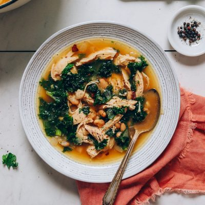 Spoon resting in a bowl of Kale White Bean Chicken Soup