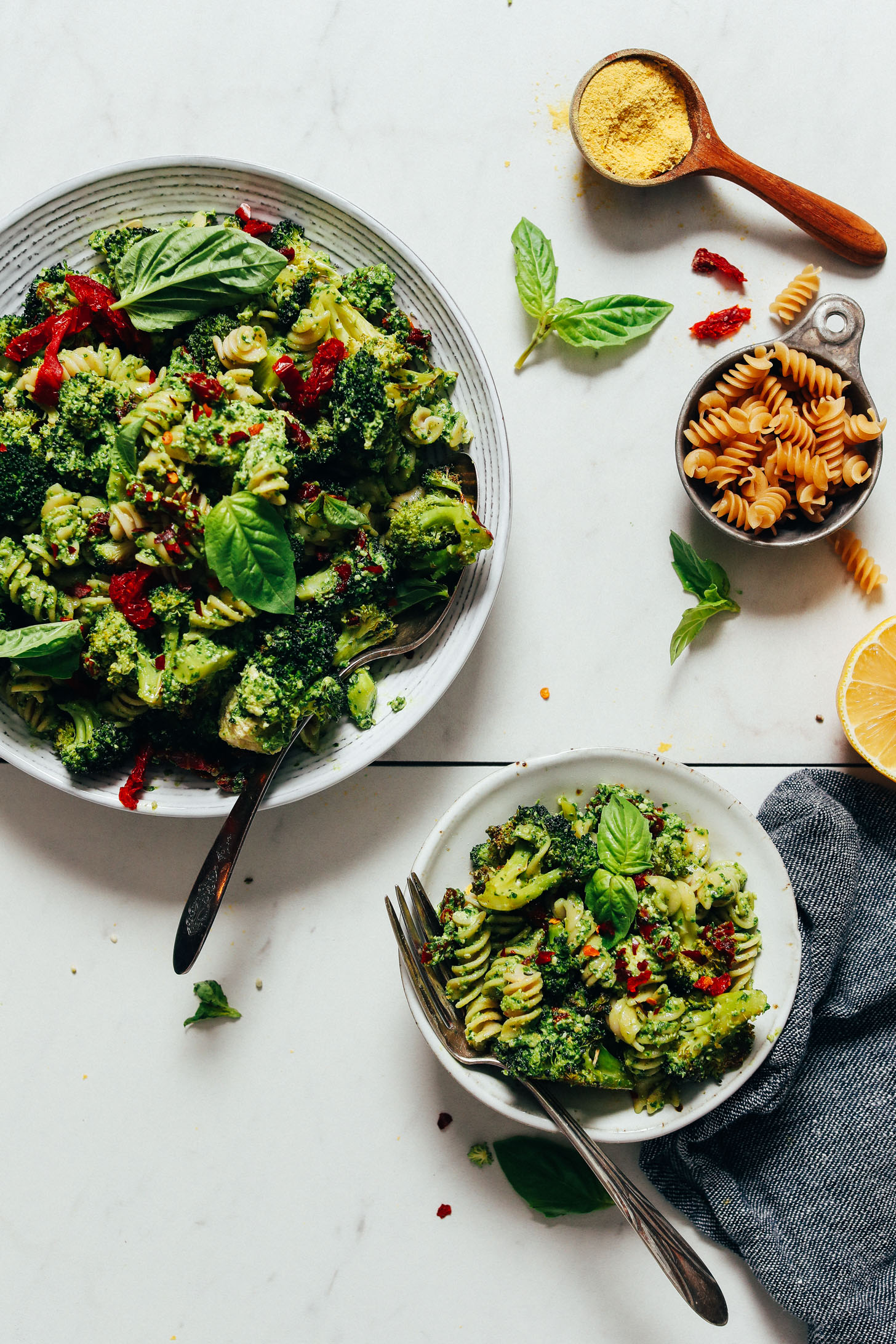Gluten-free noodles and nutritional yeast beside bowls of our Roasted Broccoli & Pasta Salad with Hemp Pesto