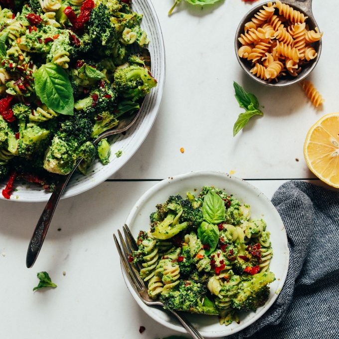 Small and large bowls of our Pesto Broccoli Pasta Salad with Sun-dried Tomatoes