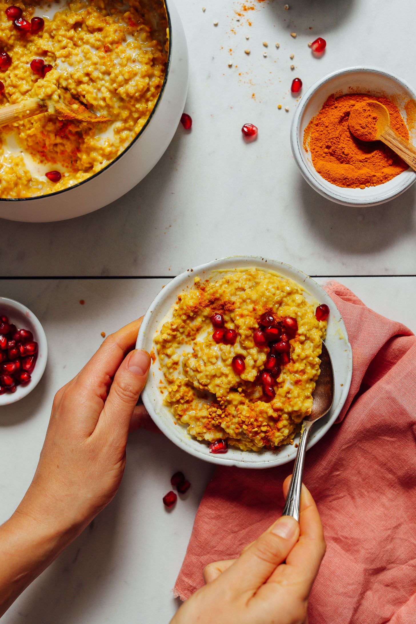 Holding a bowl of Cozy Turmeric Porridge topped with bee pollen and pomegranate seeds
