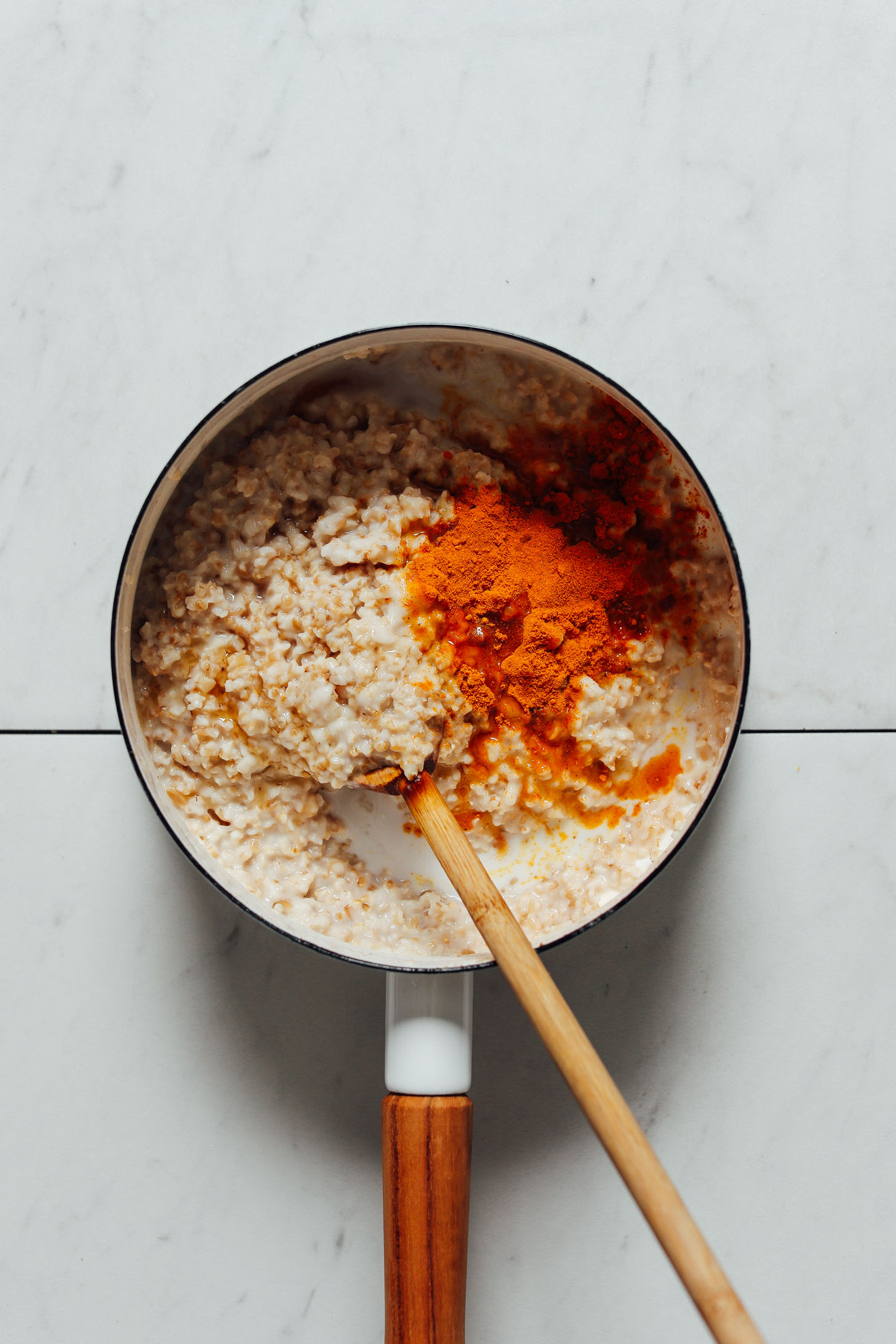 Wooden spoon in a saucepan of our Turmeric Porridge recipe