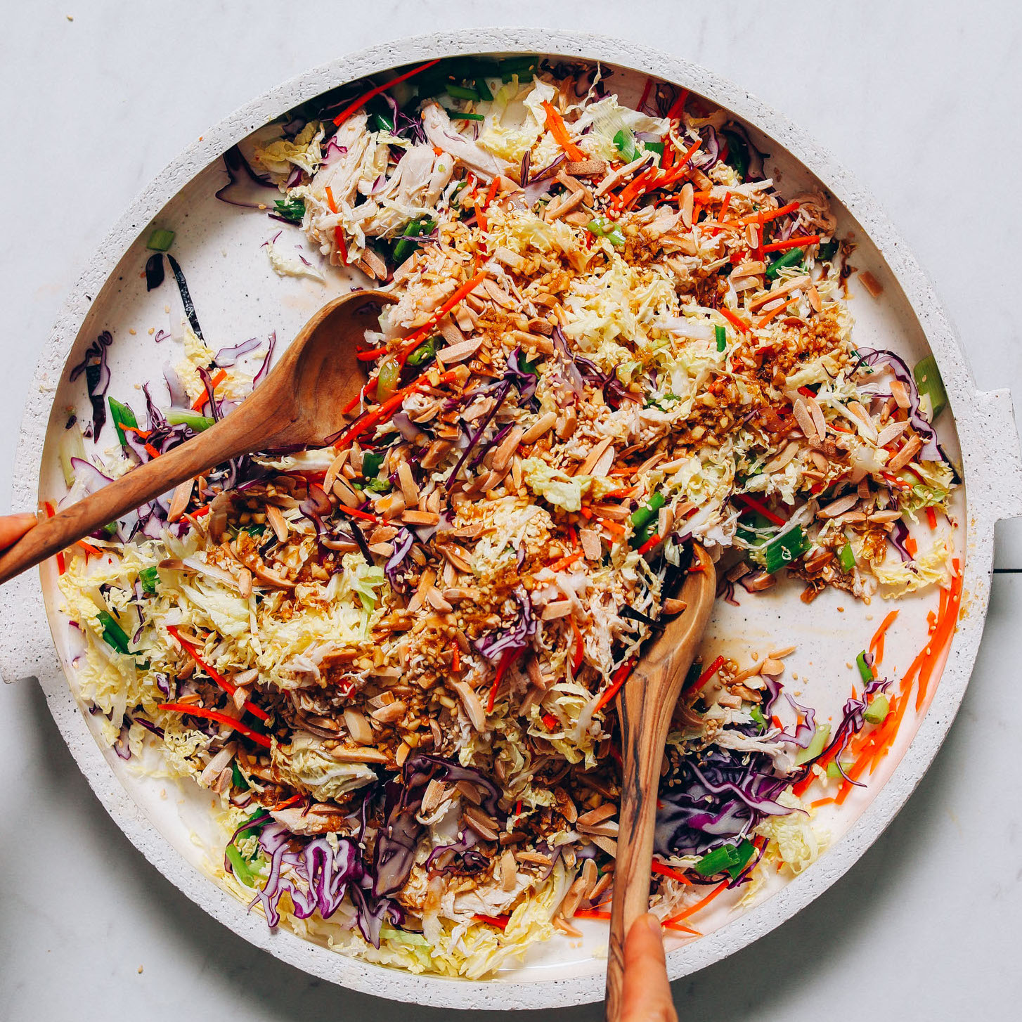 Using salad tongs to pick up a serving of gluten-free Crunchy Cabbage Slaw with Sesame Ginger Dressing