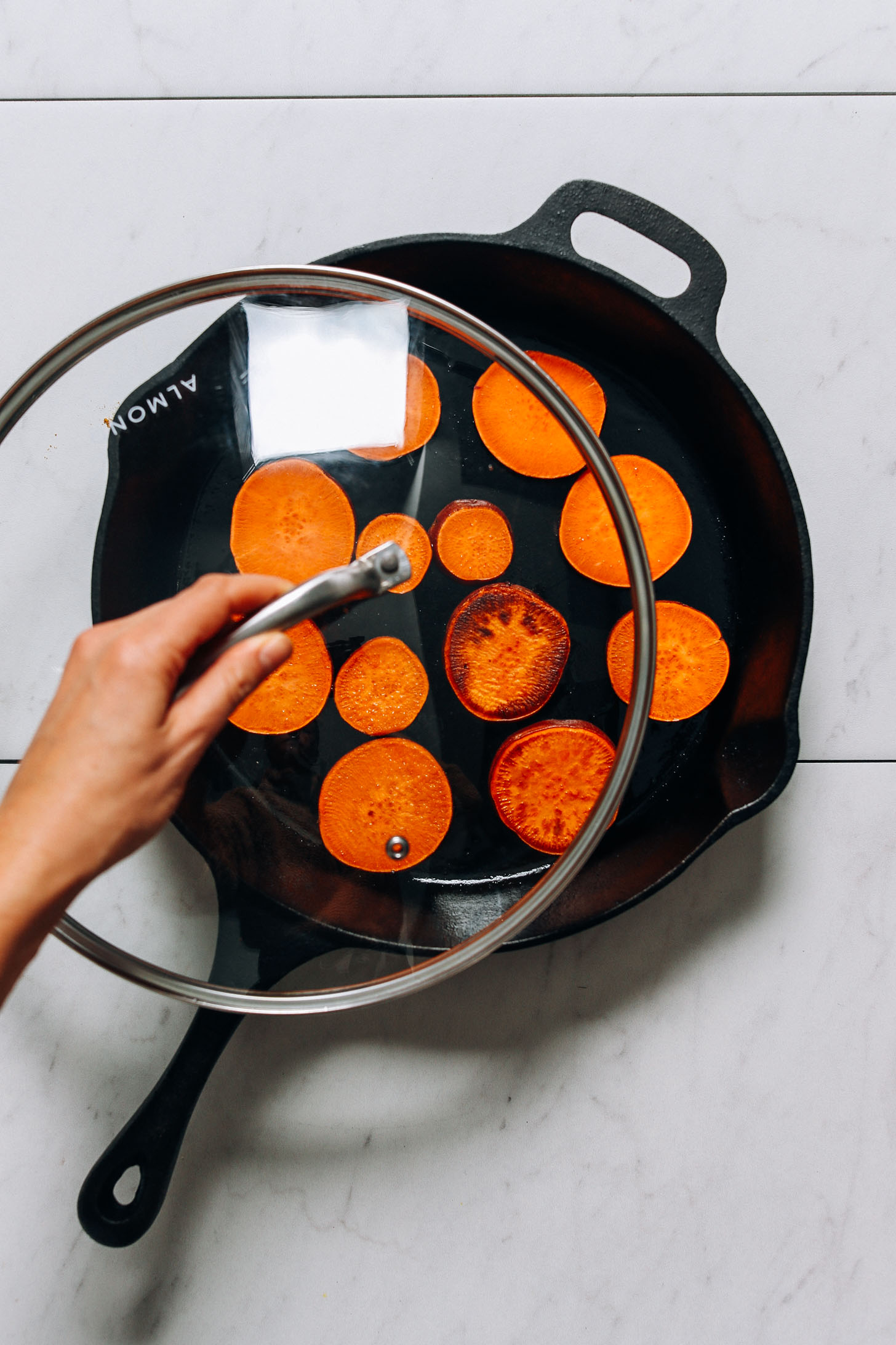 Covering a pan of sweet potatoes to help them cook through fully