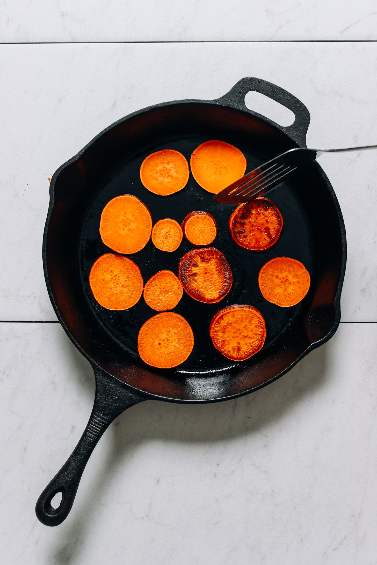 Cooking sweet potato slices in a cast iron skillet