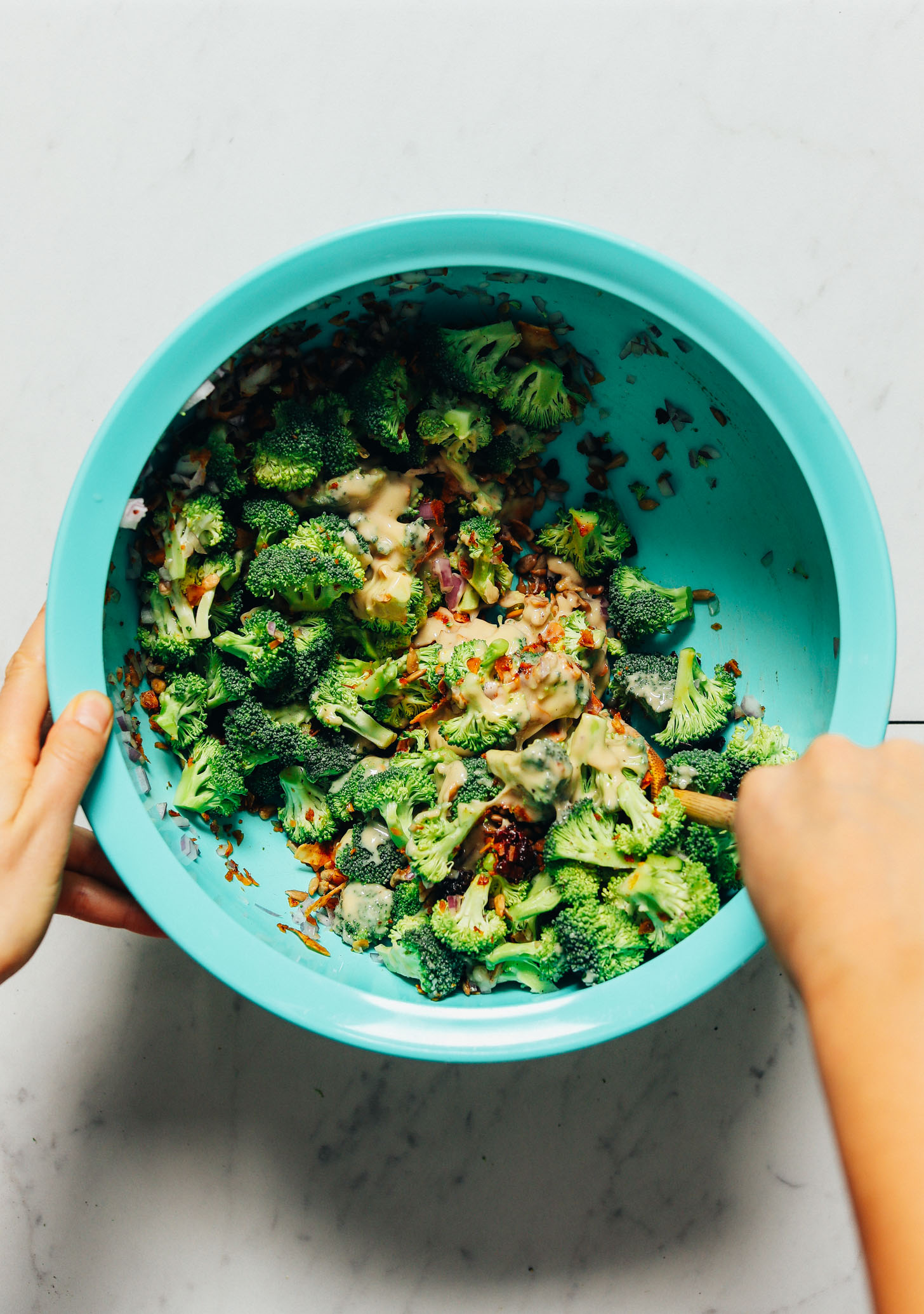 Using a wooden spoon to stir a mixing bowl of Creamy Vegan Broccoli Salad
