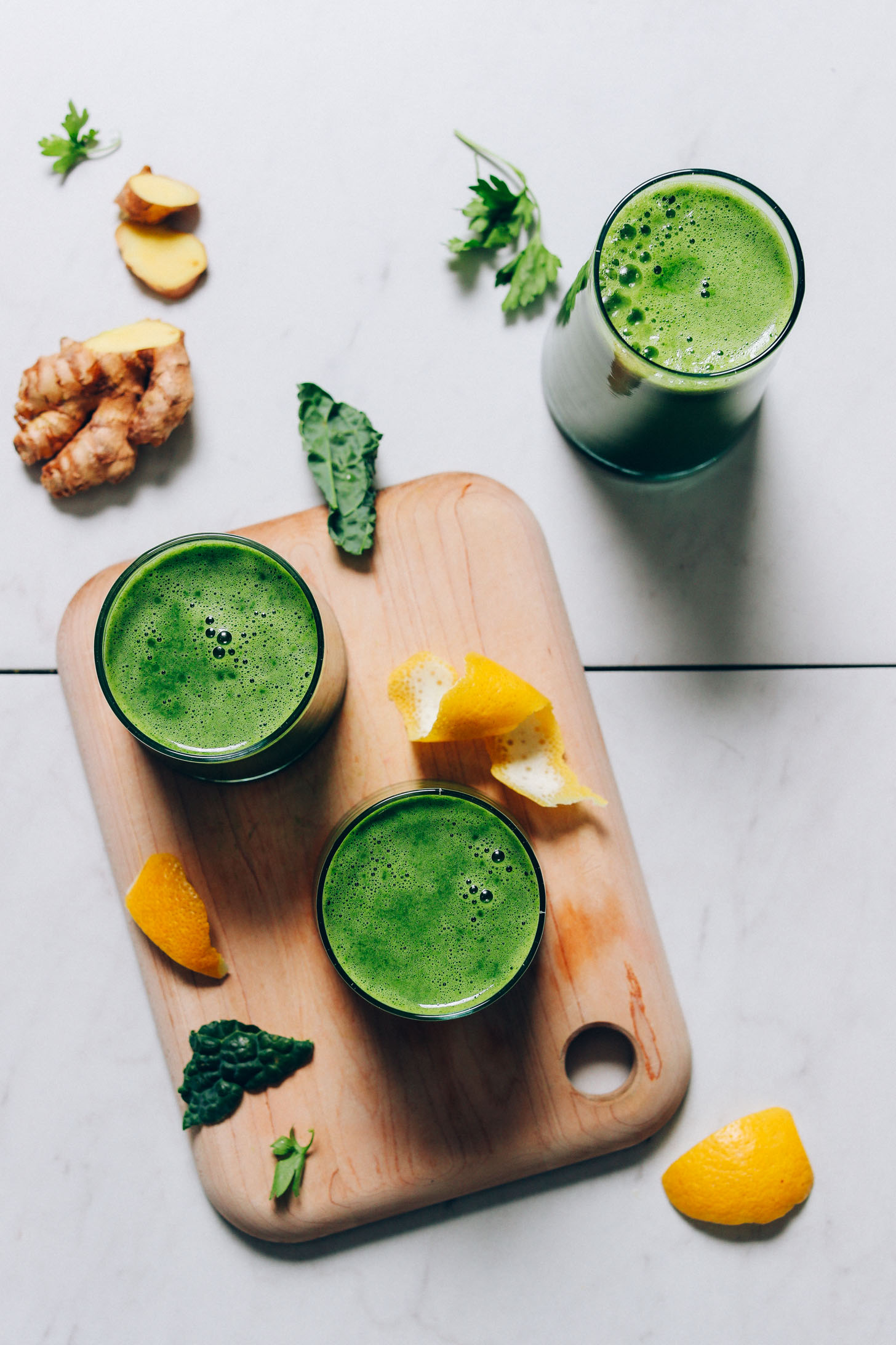 Glasses of homemade Green Juice on a cutting board beside ingredients used to make it