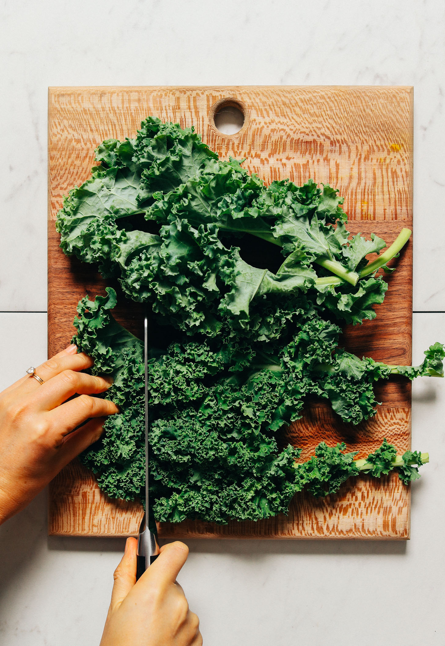 Using a large knife to chop kale for our Massaged Kale Salad recipe