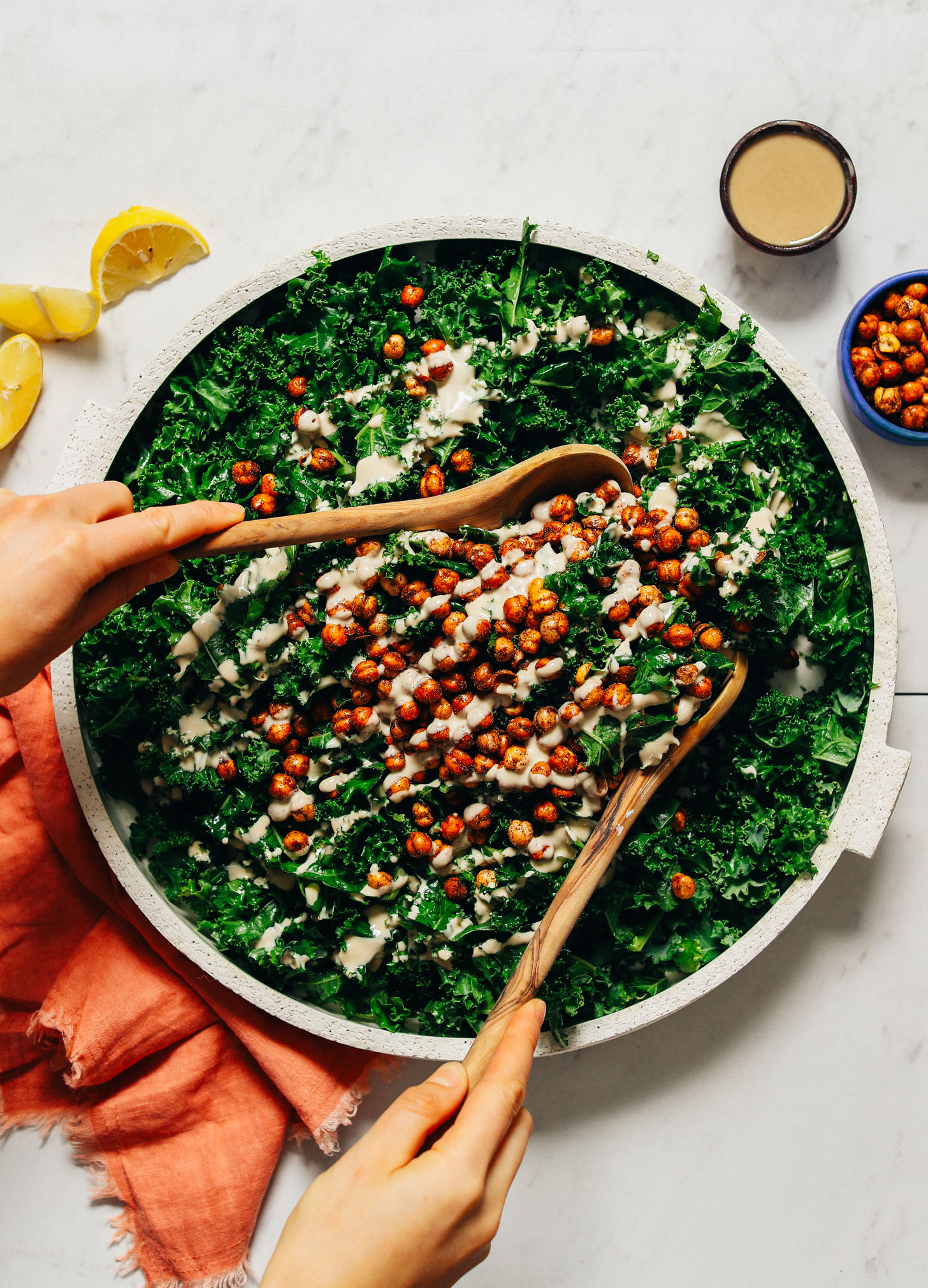 Platter of Massaged Kale Salad topped with Crispy Baked Chickpeas and tahini dressing