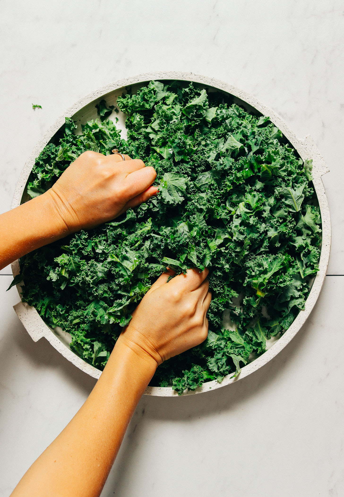 Massaging kale on a large platter