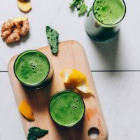 Cutting board with glasses of green juice and ingredients used to make it