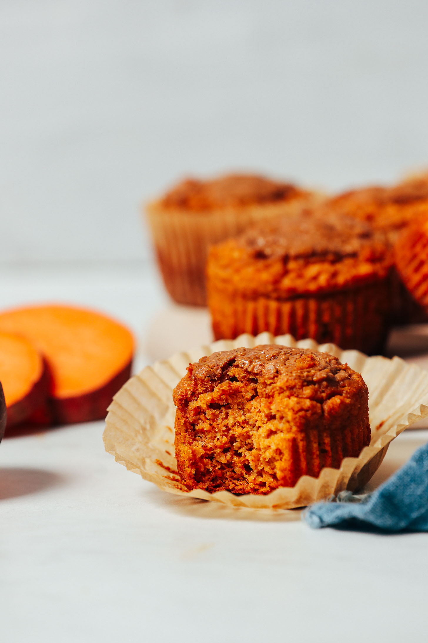 Partially eaten Almond Butter Sweet Potato Muffin beside sliced sweet potato rounds