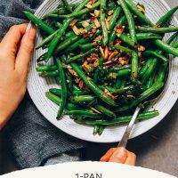 Holding a spoon in a big bowl of Garlicky Green Beans with Slivered Almonds