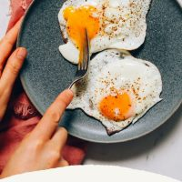 Plate with two perfectly cooked sunny-side up eggs for our tutorial on How to Cook Eggs