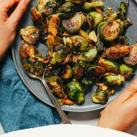 Holding a plate of Miso-Glazed Brussels Sprouts with recipe text below it