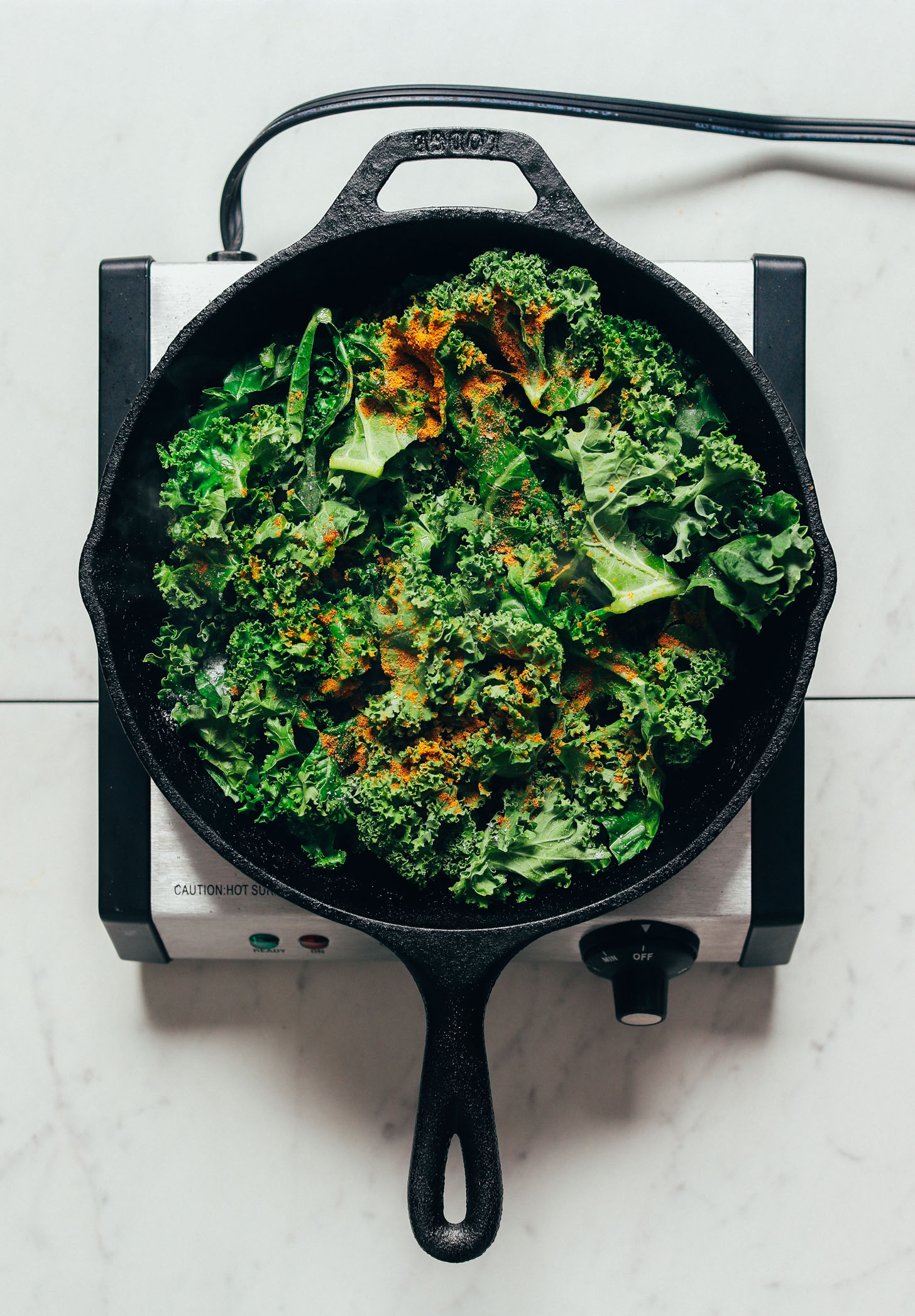 Skillet filled with kale and sprinkled with curry powder