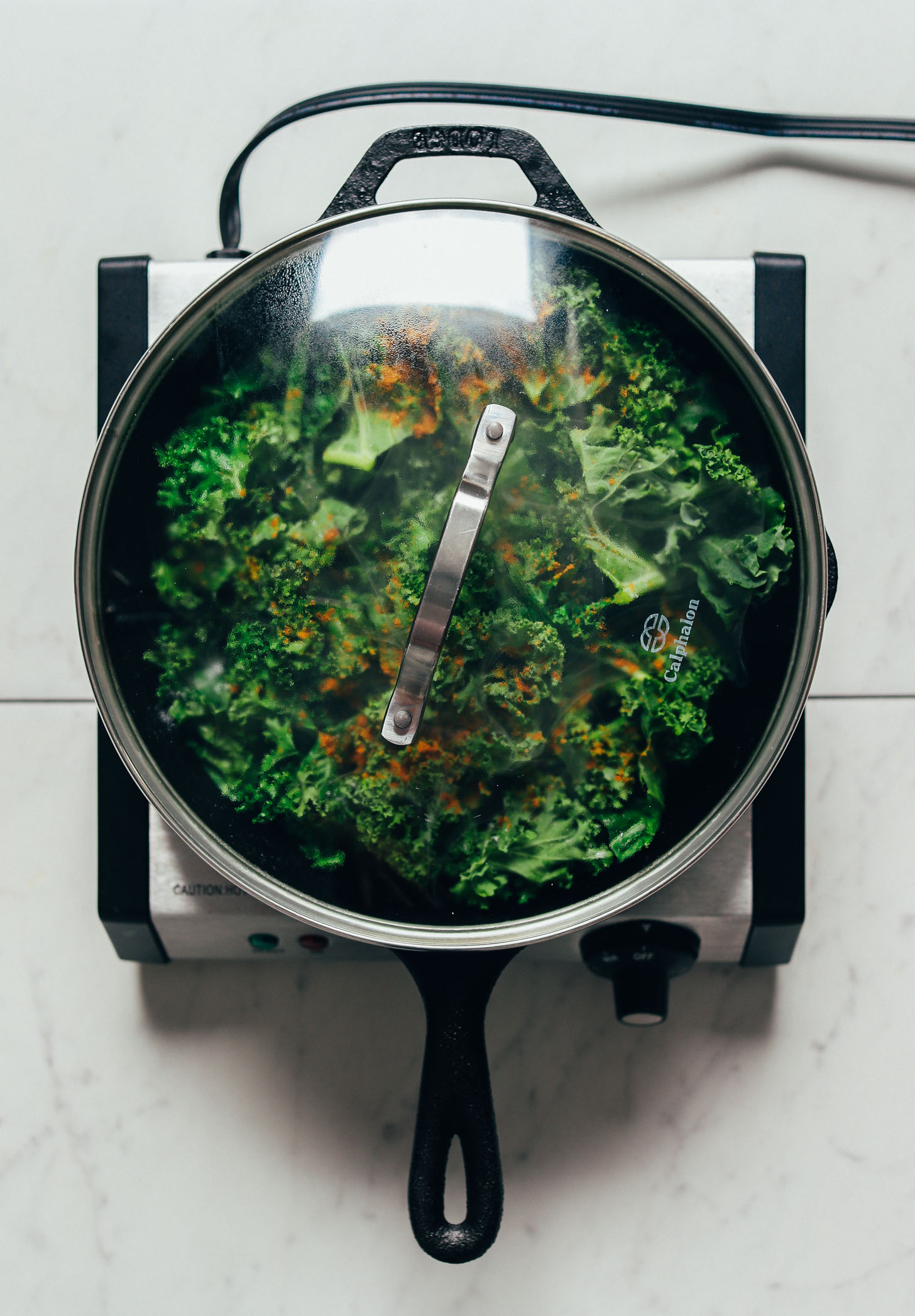Covered pan of kale with curry powder for our simple Sautéed Kale recipe