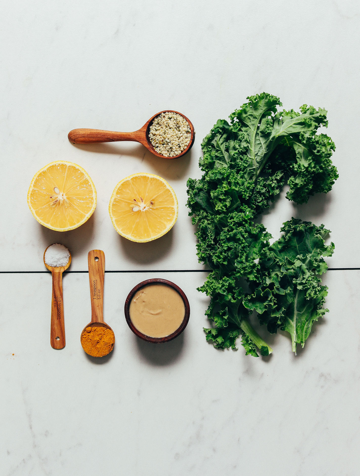 Kale, hemp seeds, lemon, tahini, curry powder, and salt for making our easy sautéed kale recipe