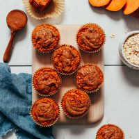 Cutting board filled with Almond Butter Sweet Potato Muffins beside ingredients used to make them