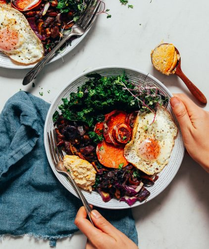 Holding a Breakfast Bowl filled with mushrooms, kale, cabbage, eggs, and sweet potato