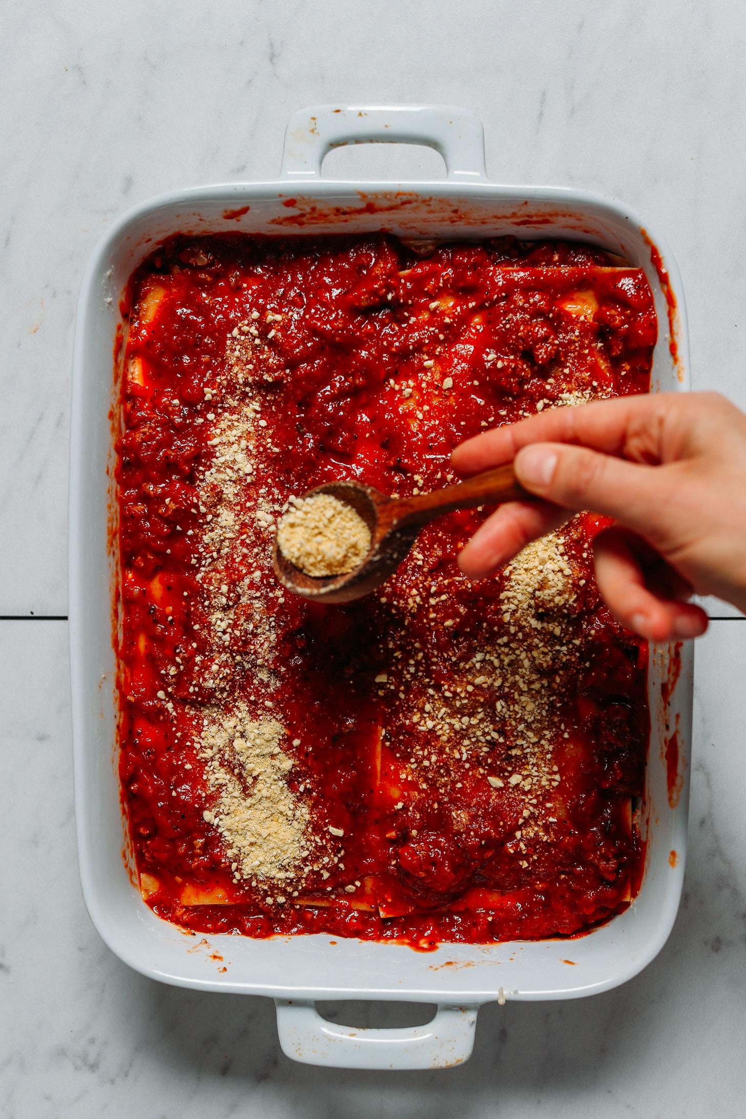 Sprinkling vegan parmesan cheese onto a pan of our gluten free lasagna
