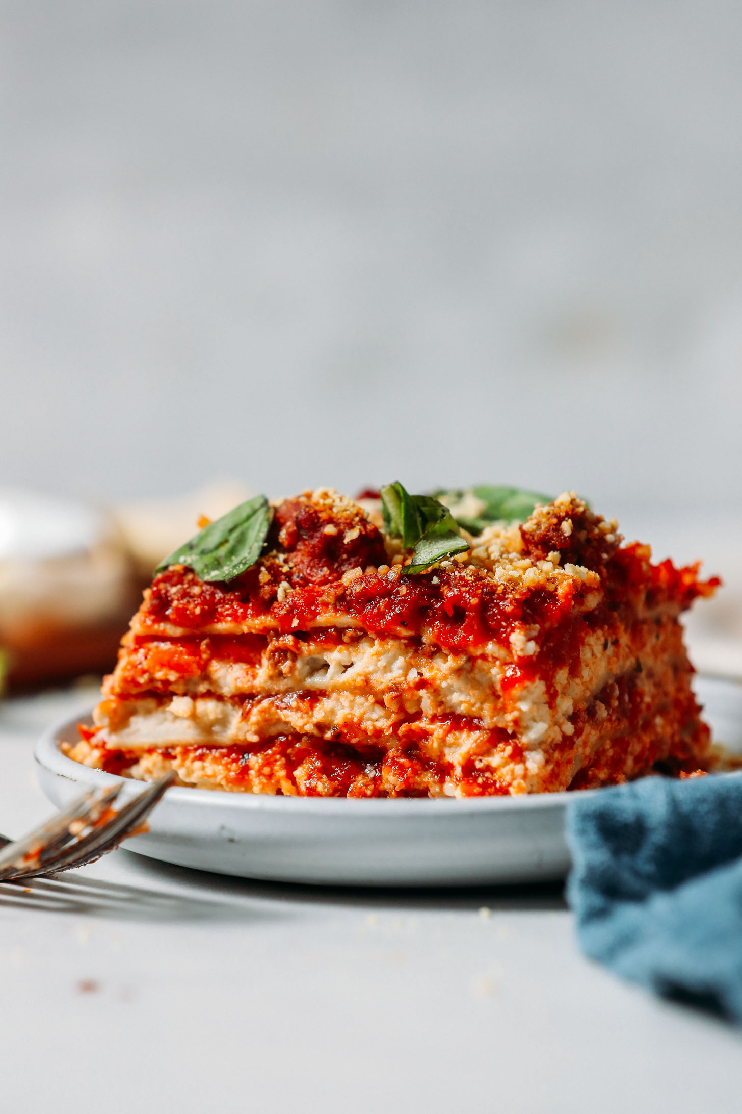Side view of a slice of Dairy-Free Gluten-Free Lasagna topped with vegan parmesan and fresh basil
