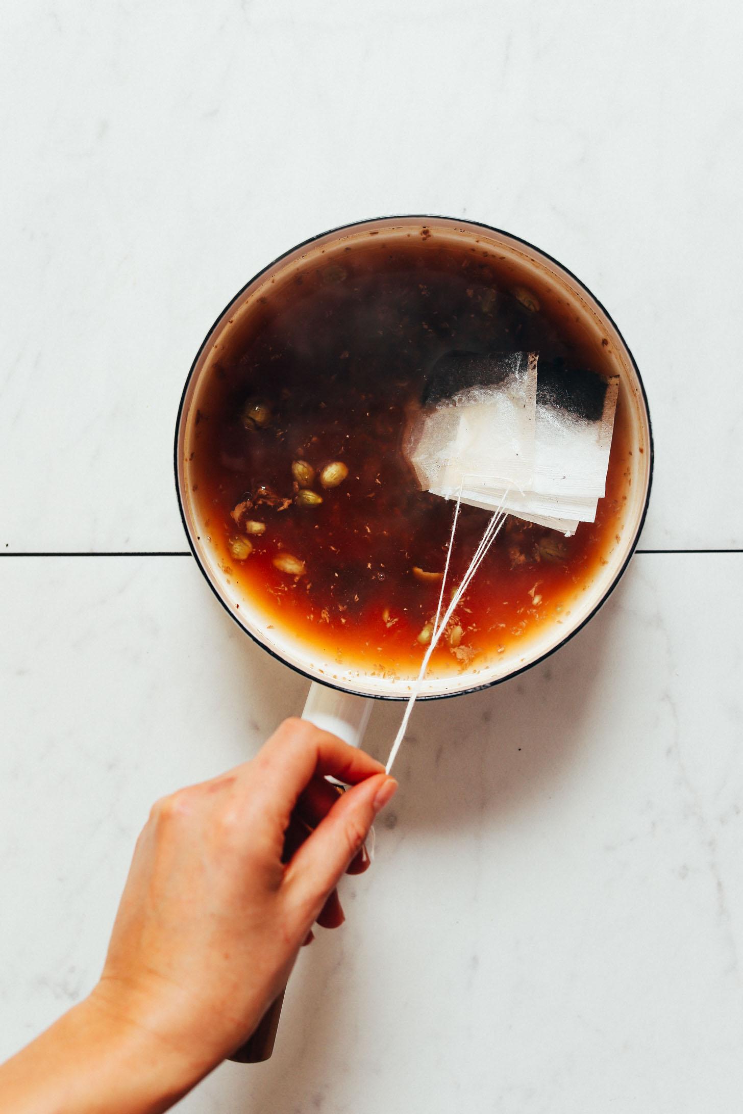 Bolsitas de té en una cacerola con especias para hacer nuestra receta Masala Chai
