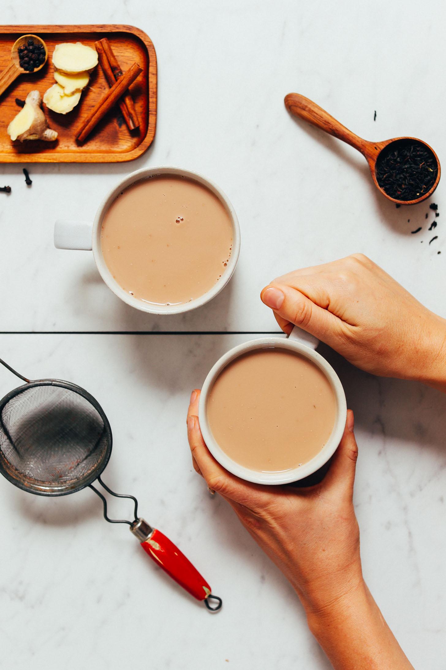 Sosteniendo una taza de té Masala Chai casero junto a los ingredientes utilizados para prepararlo