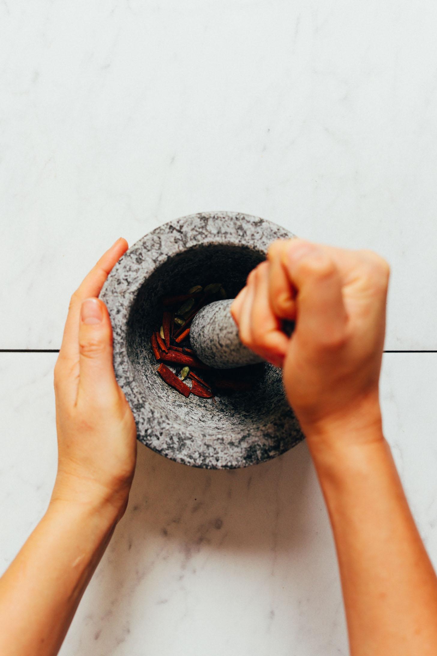 Usando un mortero y una mano de mortero para moler ligeramente las especias enteras para hacer té Chai casero