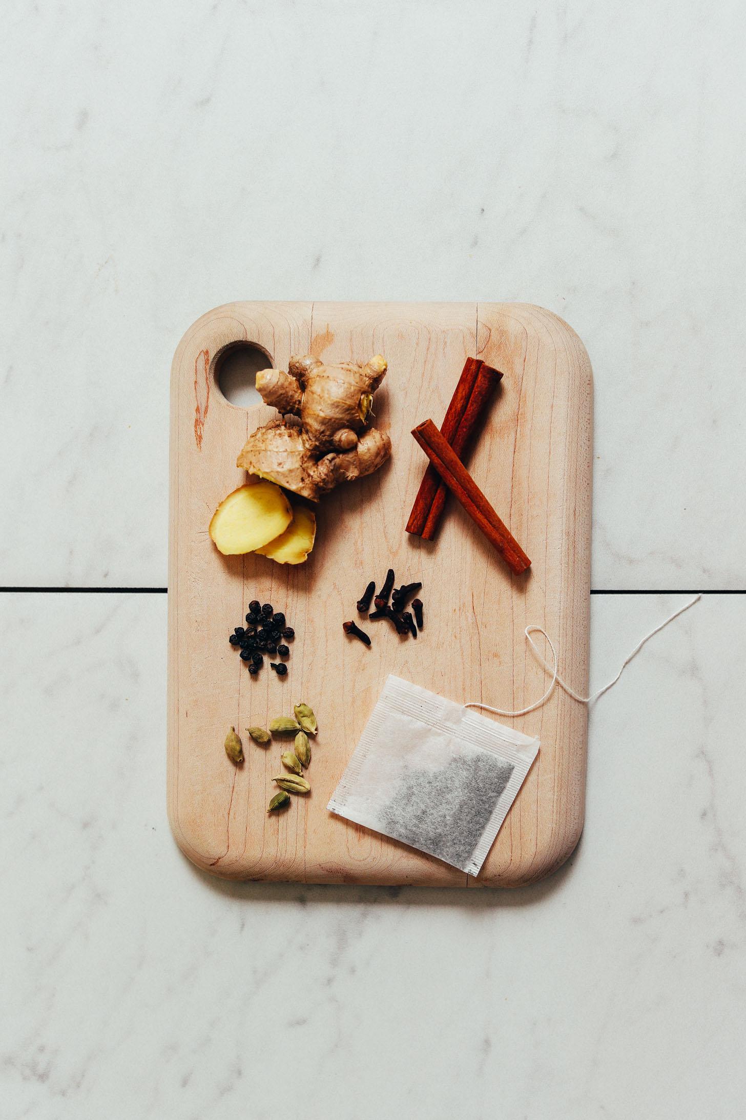 Ginger, cinnamon sticks, cloves, black pepper, cardamom pods, and black tea for making our homemade Chai Tea Recipe