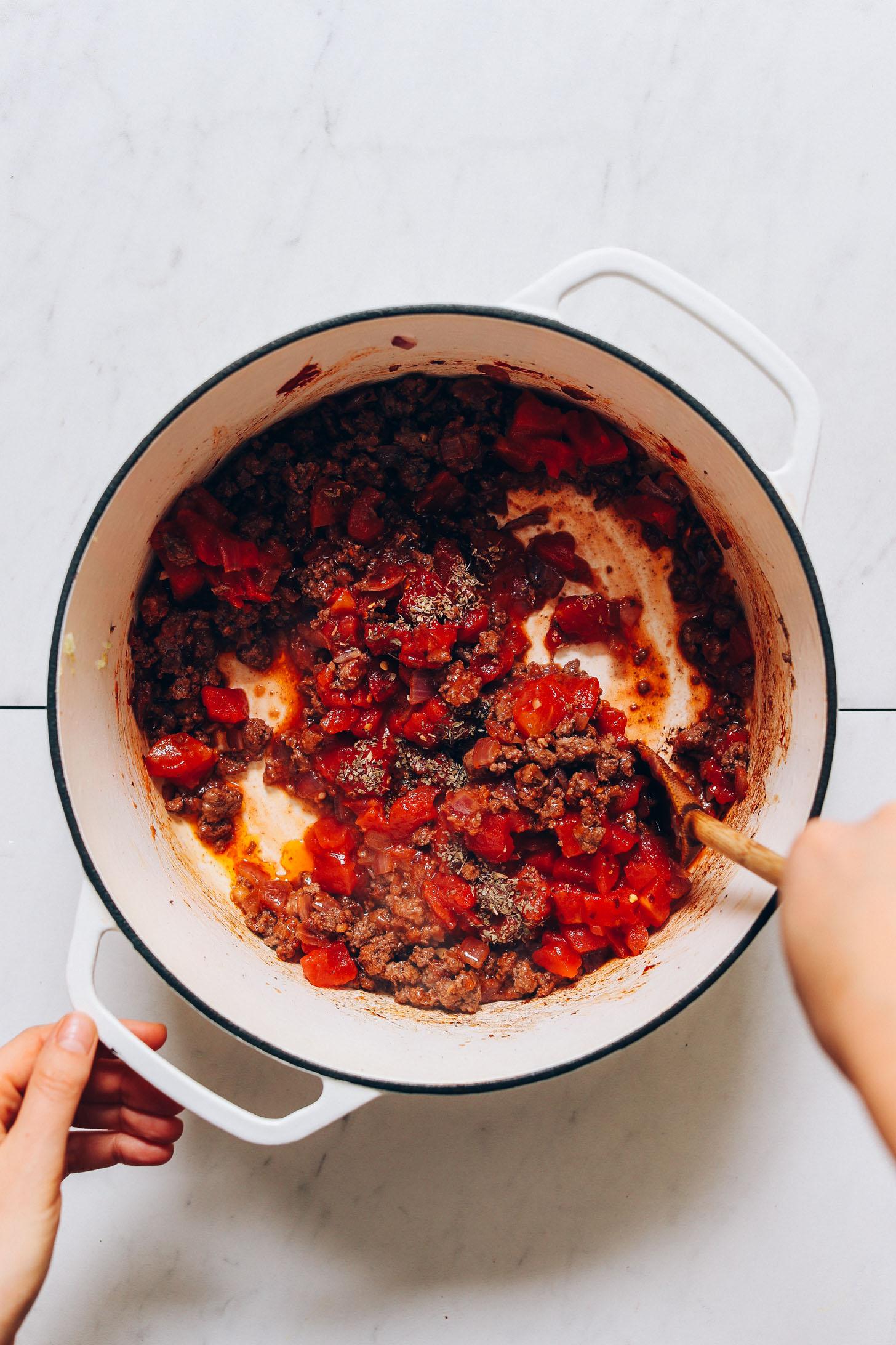 Revuelva la carne molida y los tomates para nuestra receta de sopa de carne y lentejas al estilo toscano