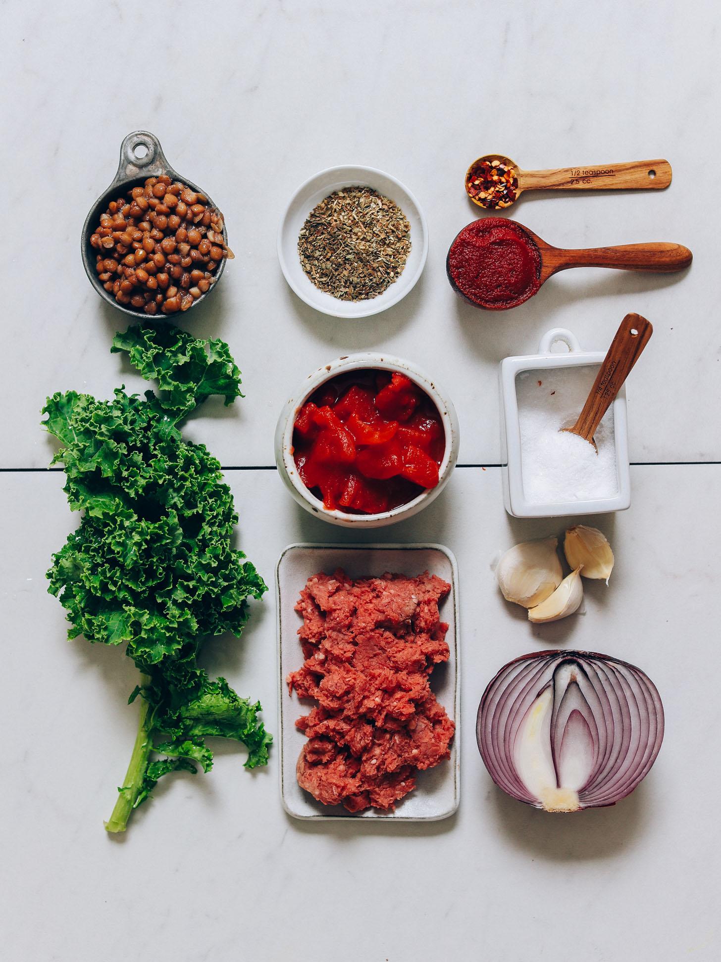 Col rizada, lentejas, tomates, hierbas, cebolla, ajo, sal y carne molida para hacer nuestra sopa de carne y lentejas al estilo toscano.