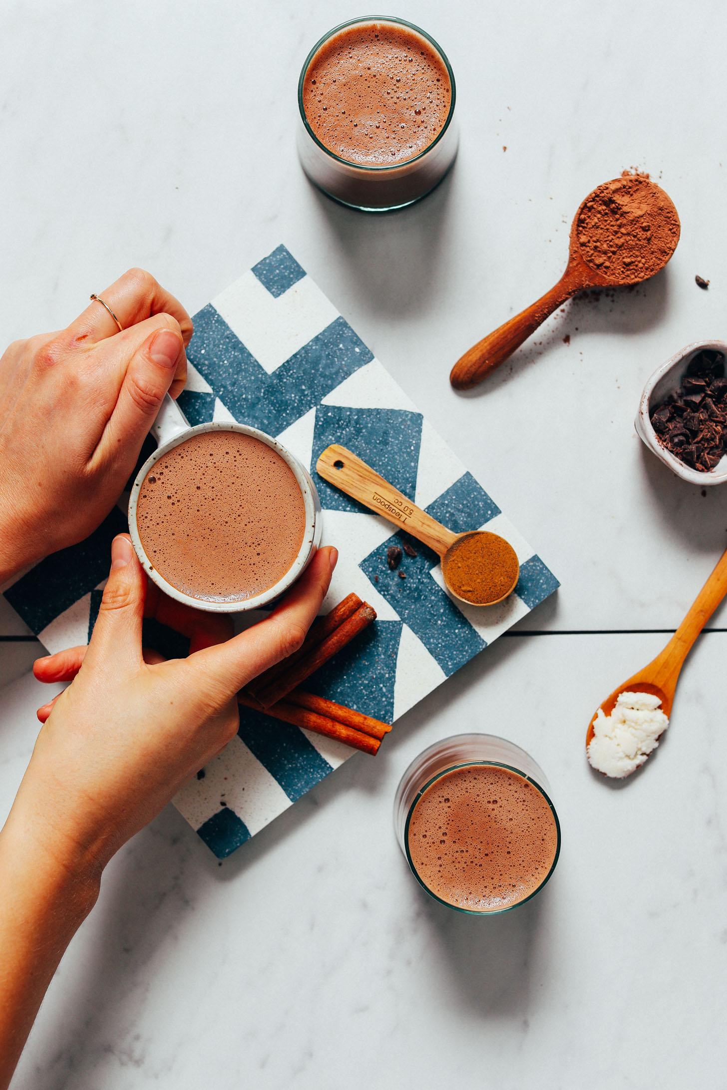 Sosteniendo una taza de chocolate caliente adaptogénico elaborado con nuestra receta de mezcla