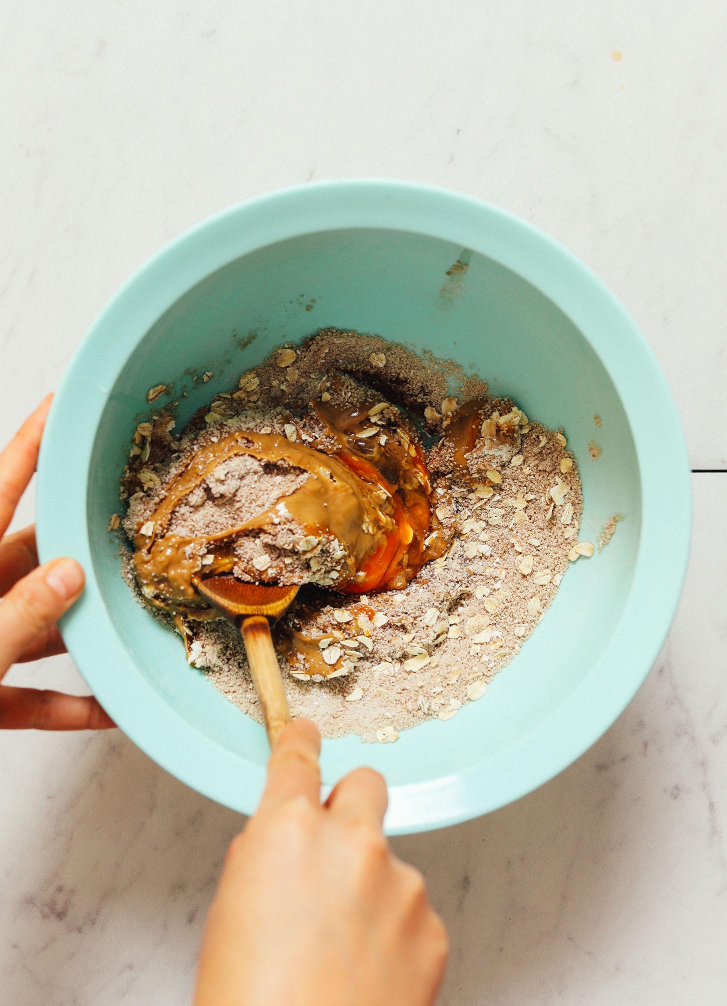 Usando una cuchara de madera para remover la masa de galletas de chispas de chocolate y mantequilla de maní sin gluten