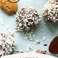 Almond Butter Dark Chocolate Snowballs on a parchment-lined baking sheet