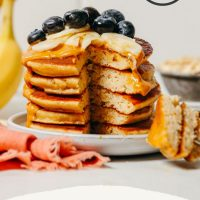 Bite removed from a stack of Gluten-Free Blender Banana Pancakes topped with fresh blueberries and banana