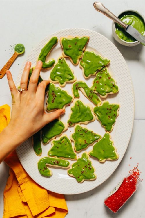 Placing a Grain-Free Sugar Cookie onto a platter of other Christmas cookies