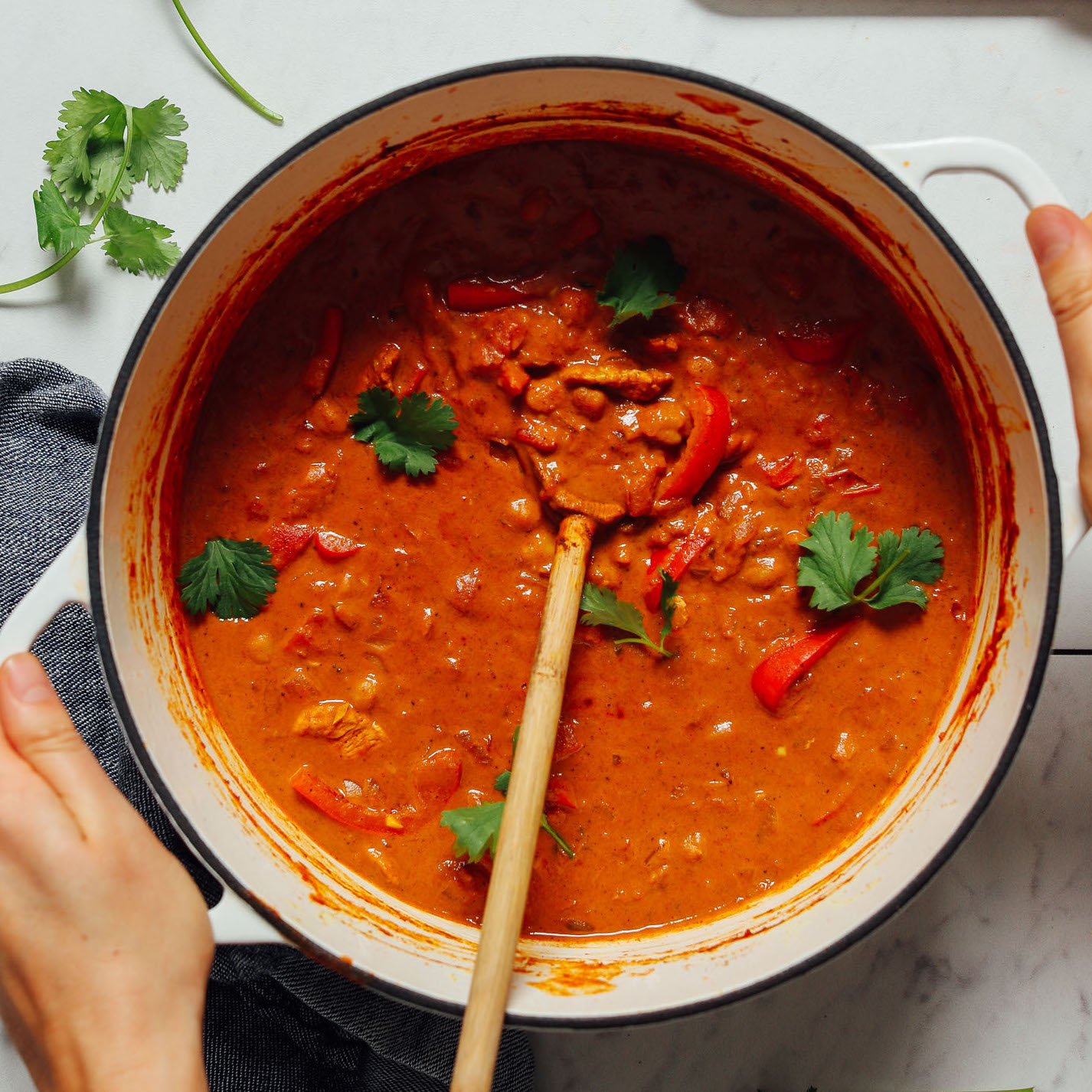 lifting a pot of Tikka Masala garnished with cilantro sprigs and shown with a wooden serving spoon