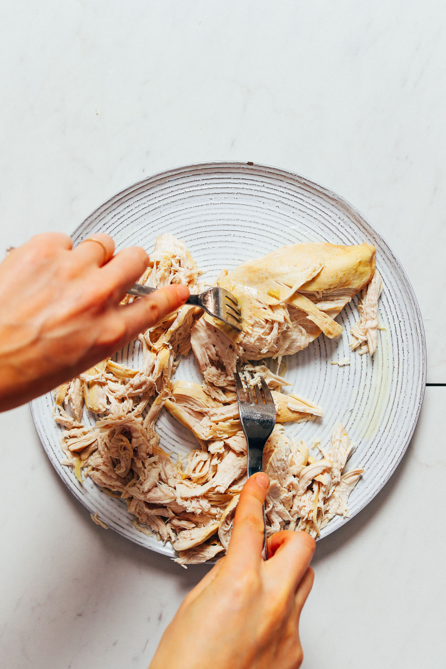 Using two forks to shred chicken breasts for Thai Chicken Noodle Soup