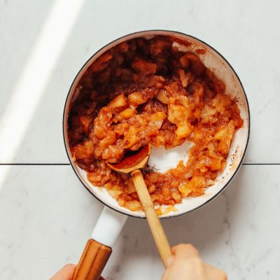 Using a wooden spoon to stir a pan of our easy Applesauce recipe