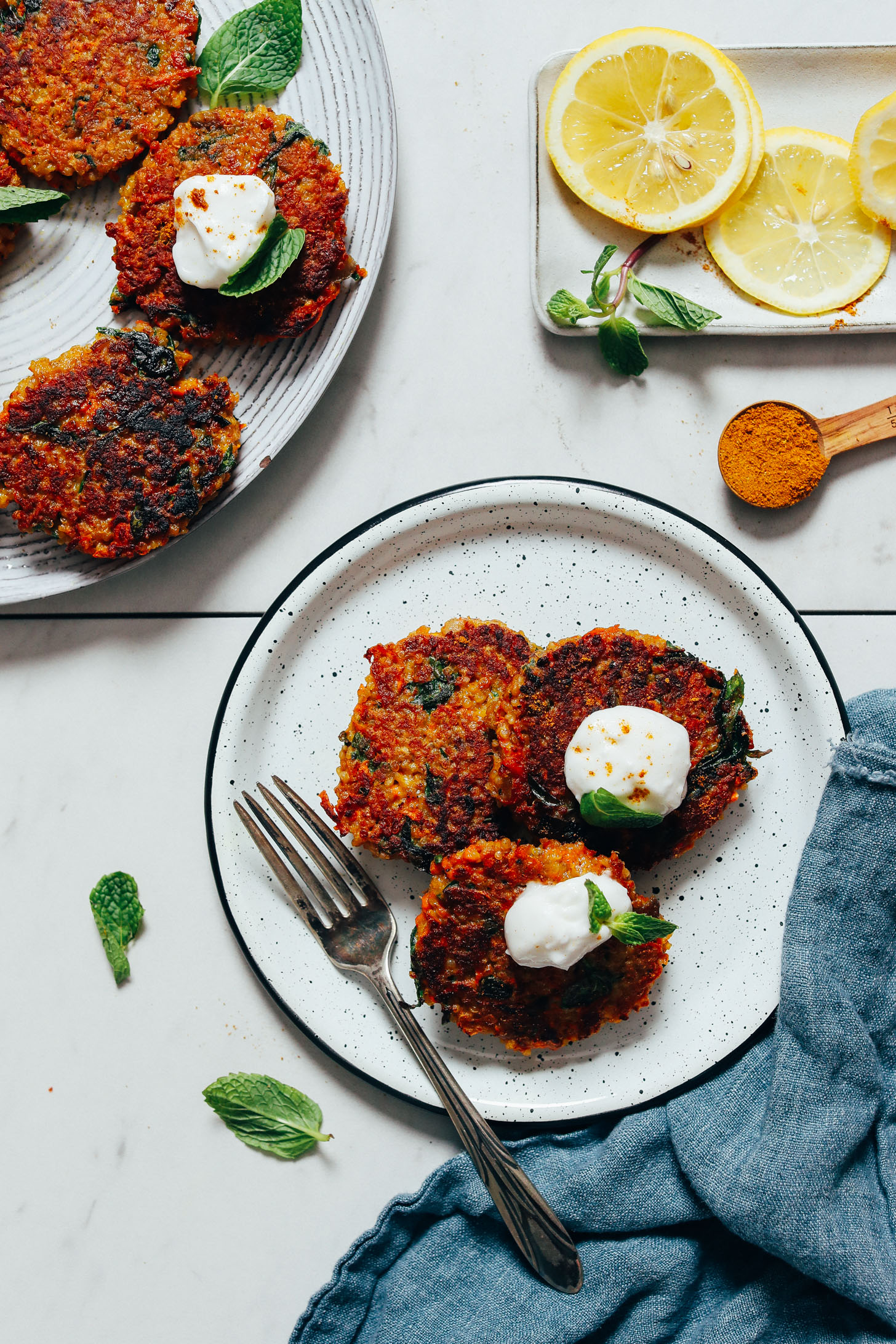 Plate of Quinoa Sweet Potato Fritters topped with dairy-free yogurt and fresh mint