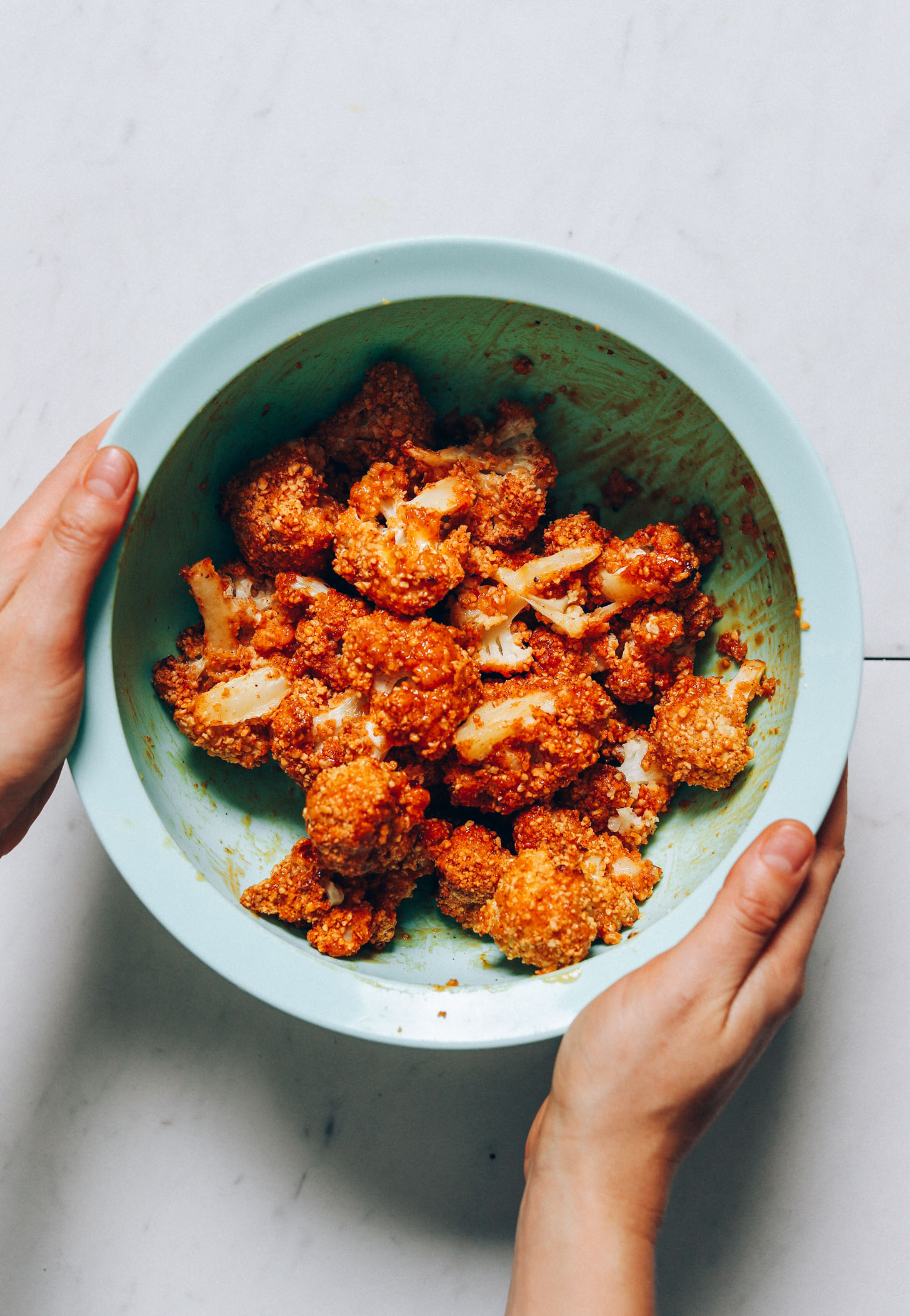 Holding the sides of a bowl of Crispy Breaded Cauliflower Wings topped with a sweet and spicy glaze