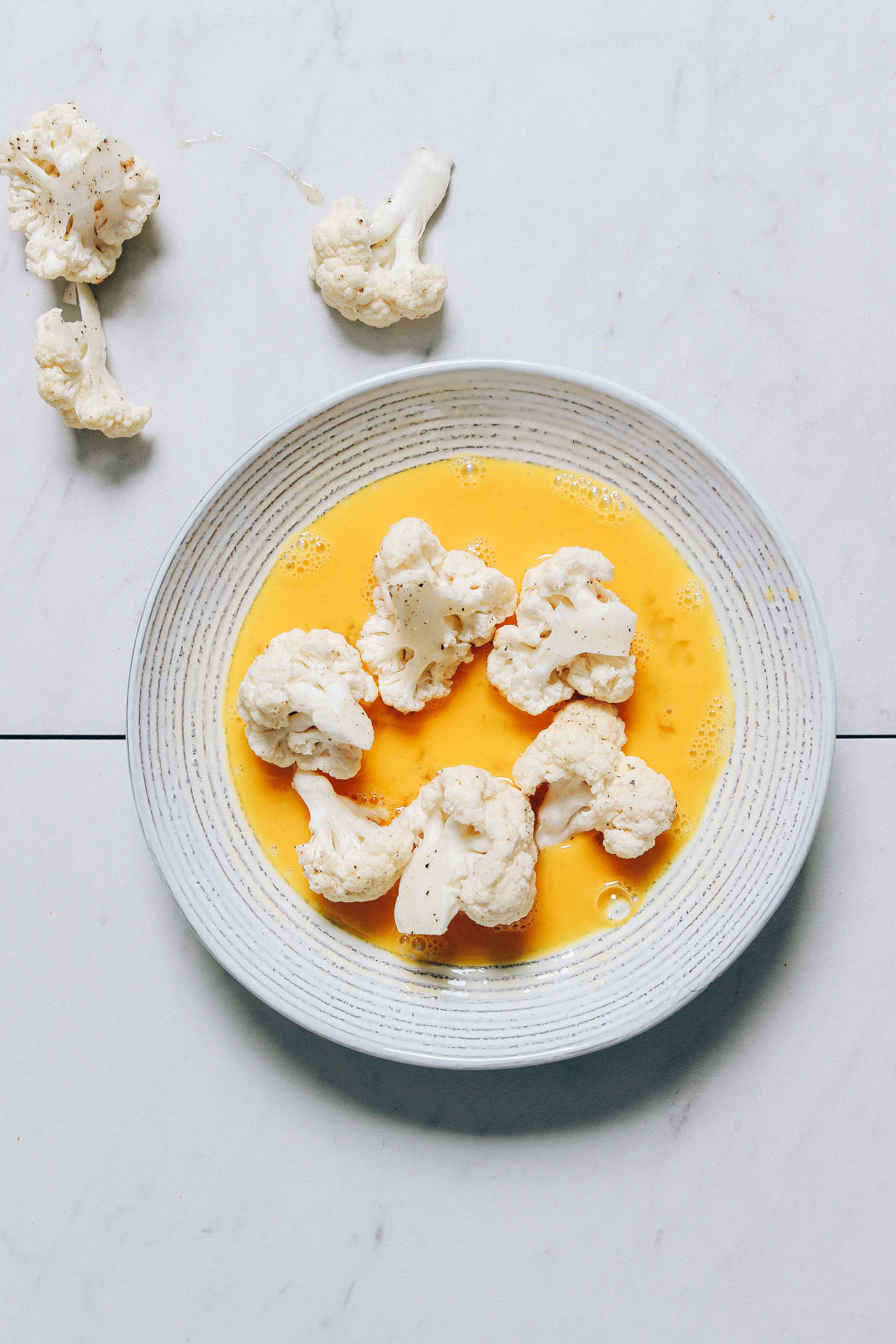 Cauliflower florets in a bowl of raw egg to help the cashew batter stick