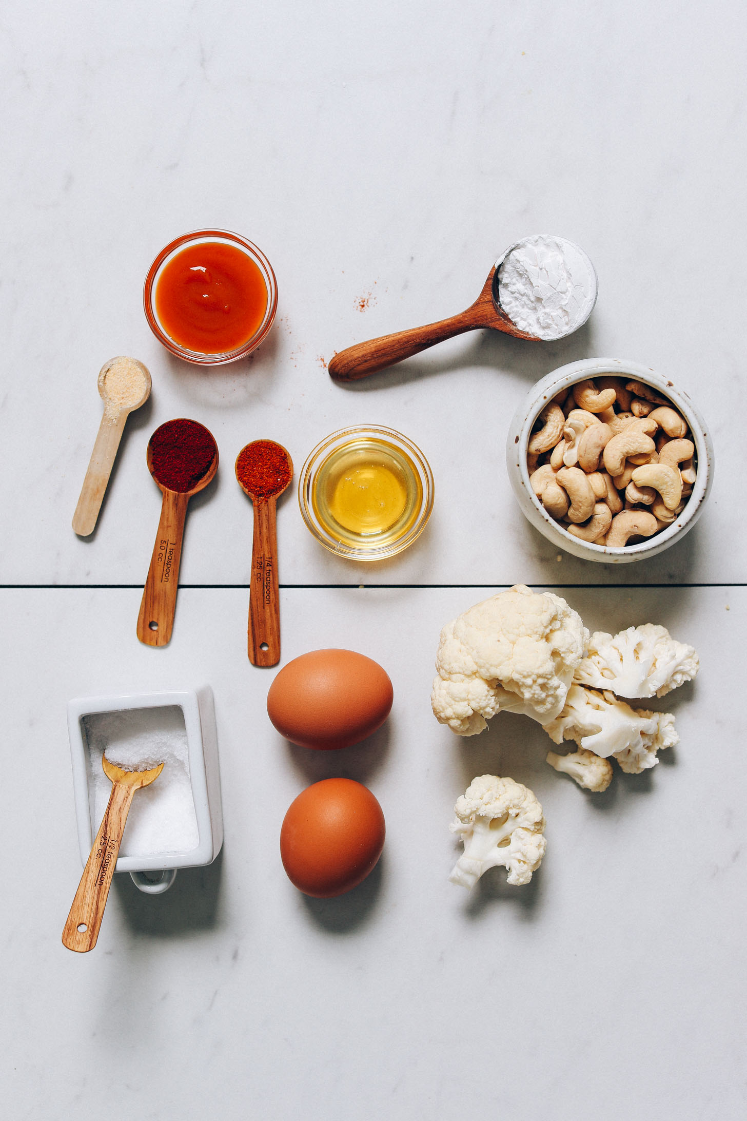 Cauliflower, cashews, eggs, honey, hot sauce, and other ingredients for making our Crispy Breaded Cauliflower recipe