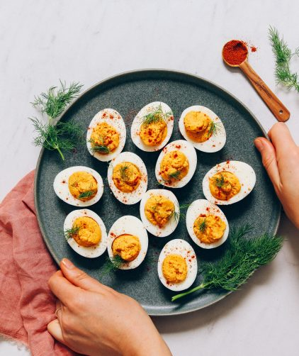 Holding the sides of a plate of Mayo-Free Deviled Eggs
