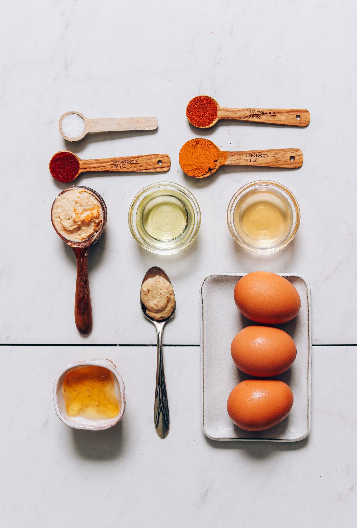 Huevos duros, hummus, miel cruda y otros ingredientes para hacer nuestra receta de Huevos Rellenos sin Mayo