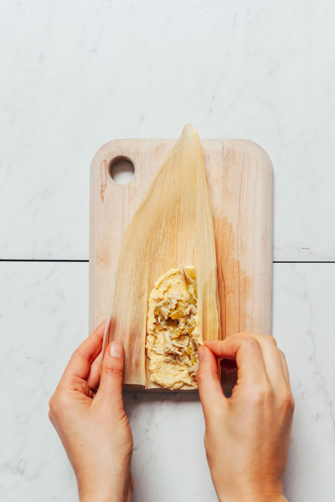 Overhead image of a corn husk on a cutting board with masa and green chile chicken filling, and two hands wrapping