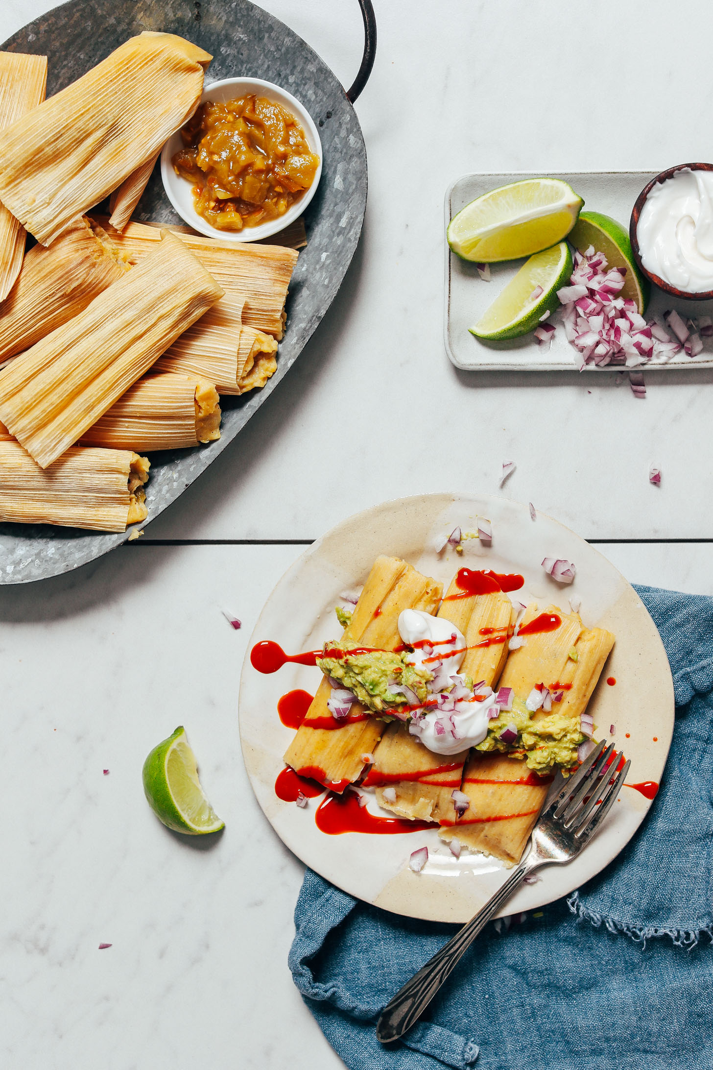 Platter of tamales next to a plate of Green Chile Chicken Tamales topped with guacamole, coconut yogurt, red onion, and hot sauce