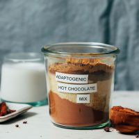 Jar of Adaptogenic Hot Chocolate Mix next to dairy-free milk and ingredients used to make it